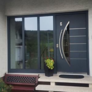dunkelgraue Aluminium-Haustür mit Seitenteil aus Glas